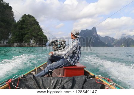 Suratthani Thailand - April 14 2015: Boat driver was on the back of long tail boat  speeding on green water of dam called 'Ratchaprapha' in Suratthani Thailand.