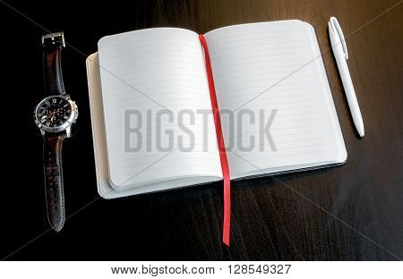 Notebook With Red Bookmark On A Dark Table With A Pen And Clock