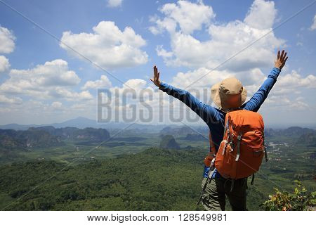 cheering woman hiker open arms on mountain peak