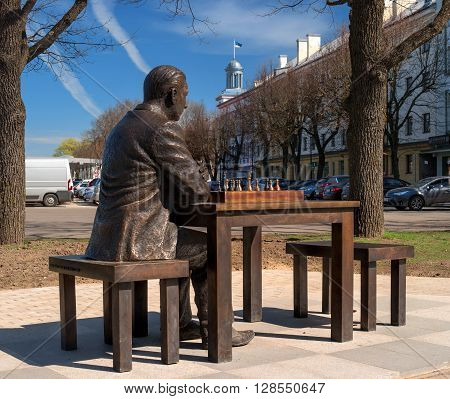 Narva Estonia - May 4 2016: monument to the famous Estonian chess player Paul Keres. Installed near Peter's Square. Building with a turret and the Estonian flag - City Government.