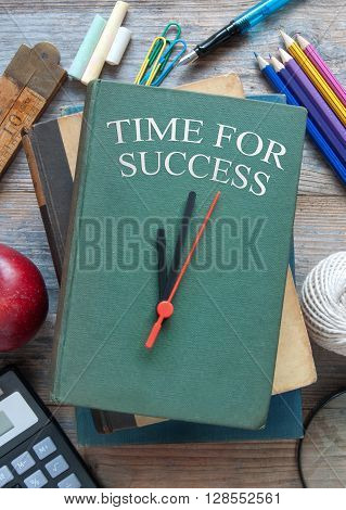 Education schooling stationery items on a wooden table with time for success clock book cover
