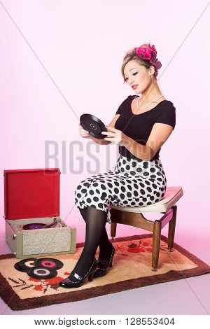 Vintage pinup style of cute blond preparing to play vinyl records