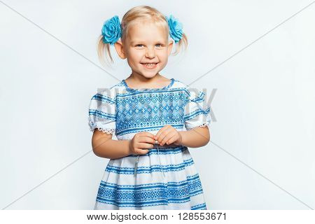 Beautiful baby blonde girl on a white background smiling