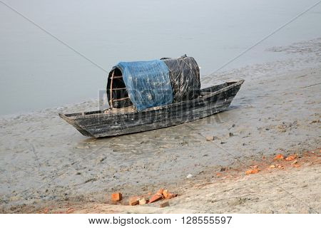 CANNING TOWN, WEST BENGAL, INDIA - JANUARY 17: Boats of fishermen stranded in the mud at low tide on the river Malta near Canning Town, India on January 17, 2009.