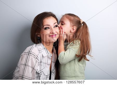 Happy Cute Kid Girl Whispering The Secret To Her Funny Grimacing Mother In Ear In Studio On Blue Bac