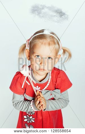 Portrait of a little girl with a toy a nimbus on her head. Girl clasped her hands in prayer