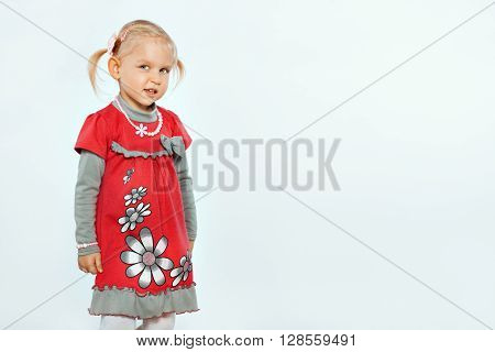 Little beautiful blond girl on a white background. Child looks slyly