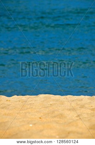 Tranquil idyllic sand beach resort shore over vivid blue sea wavy water background