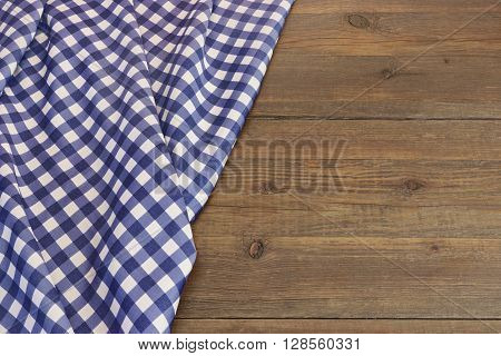 Rustic Picnic Wooden Table With Blue Folded Checkered Tablecloth