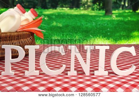 Picnic Sign On Table With Basket And Red Tablecloth