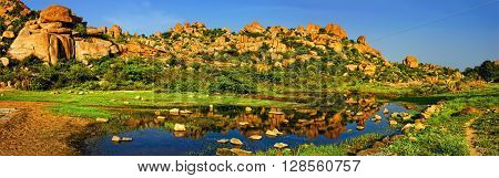 Beautiful nature scenery with bright blue lake against the background of blue sky and strange landscape with large rocks Hampi India