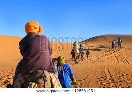 People riding on a caravan of camels in the Sahara Desert in Morocco