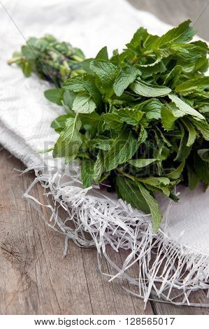 A beam of fresh mint on a wooden table. Close up photo.