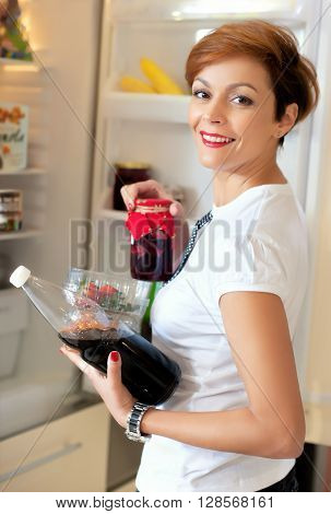 Time for lunch. Young happy smiling woman preparing some heathy food
