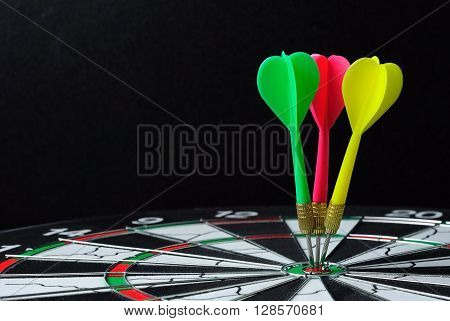 Three Darts On Bulls Eye With Black Background Horizontal Shot
