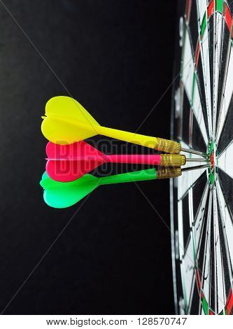 Darts On Bulls Eye With Black Background Vertical Shot