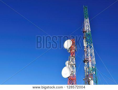 Radio station and communication towers against blue sky horizontal image.