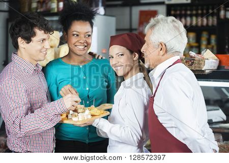 Salespeople Offering Cheese Samples To Customers In Supermarket