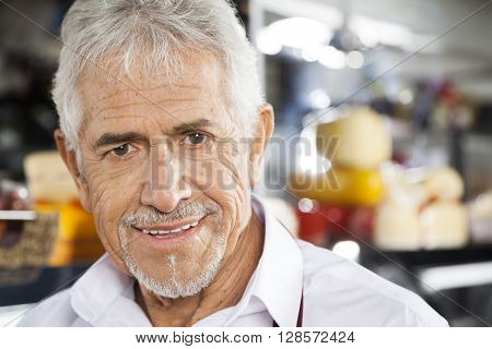 Happy Senior Salesman In Grocery Store