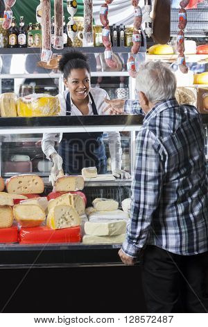 Saleswoman Taking Order From Customer At Cheese Shop