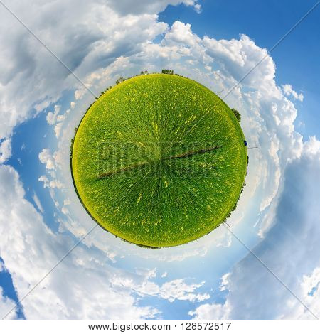 Little agricultural planet against the blue sky with clouds