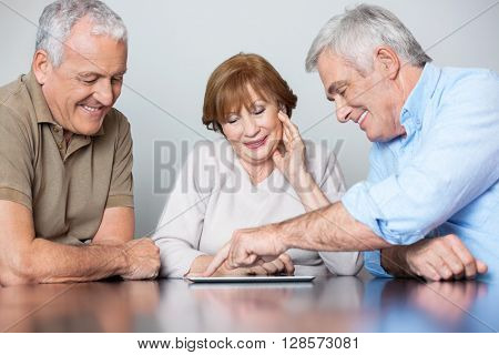 Senior Classmates Watching Man Using Tablet PC At Desk
