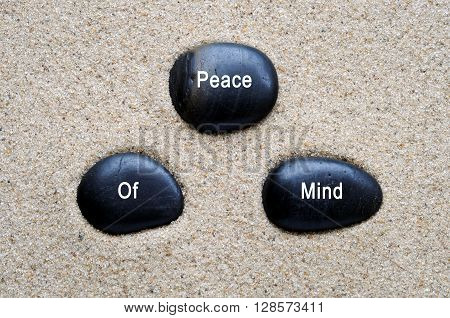 Peace of mind quotes on zen stones with sand background.