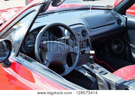 CLUJ-NAPOCA ROMANIA - APRIL 16 2016: Steering wheel and dashboard in interior of classic red Mazda MX-5 NA Series I (Mazda Miata) two-seat convertible roadster at the 2016 Retro Spring Parade.