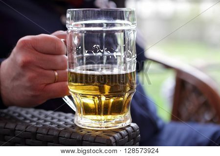 Person holding mug of beer in an outdoor cafe