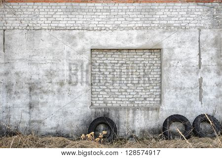 White brick and concrete wall exterior texture outside and tires next to it. Grunge background. Grunge style. The countryside. Old parts of the former use of technique. Garage. Workshop. Abandoned building. Exterior.