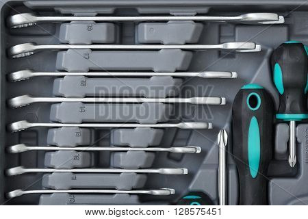 Close-up of different size wrenches and screwdrivers in open toolbox. Construction instruments and tools. Set of tools. Compact tool box. Mend and repair.