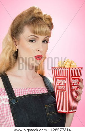 Pin up girl with carton on popcorn on a bright pink background