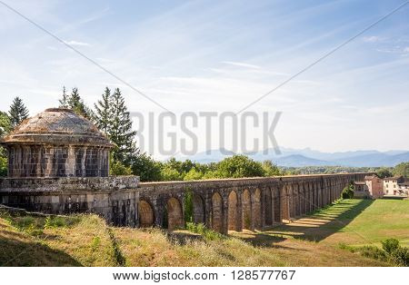 Ancient cistern in Tuscany and Nottolini Aqueduct leading past a country villa and toward the distant mountains. Copy space in sky if needed. Concepts could include Travel Architecture Europe others.