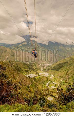 Silhouette Of Young Caucasian Man On A Swing called Flight of the Condor Banos de Agua Santa Ecuador