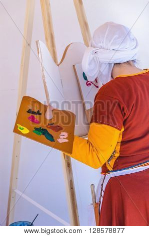 Unrecognizable woman painting on canvas in daylight