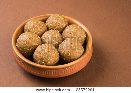 The indian sesame sweet or tilgul laddu, made up of jaggery and sesame seeds, hand made, round, indian sweet prepared in Makar Sankranti festival, served in terracotta bowl