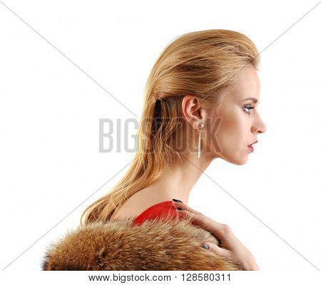 Young beautiful blonde girl wearing perfect makeup and red dress posing half-faced in a fur over white studio background