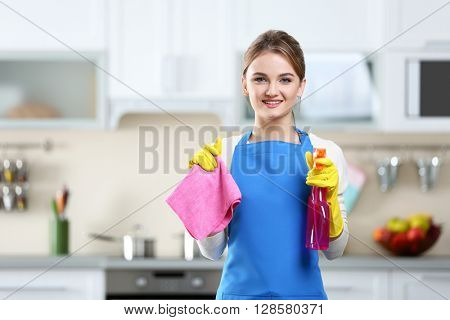 Cleaning concept. Portrait of young woman with washing fluid and rag against kitchen background