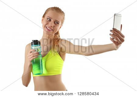 Young woman making selfie photo with sports bottle of water isolated on white