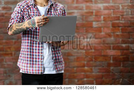 Young man with tattoo holding laptop on brick wall background