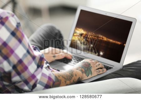 Young man with tattoo using laptop on a sofa at home