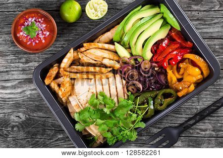 Delicious Chicken Fajita Platter with Avocado Pita Bread Bell Pepper Lime Red Onion and Cilantro bowl with salsa sauce close up top view