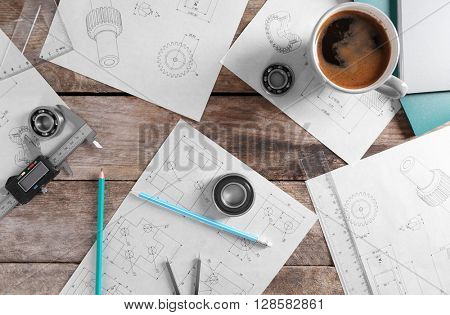 Set of engineering drawings with cup of coffee and tools, top view