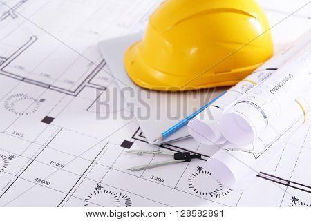 Construction blueprints with tools and helmet closeup