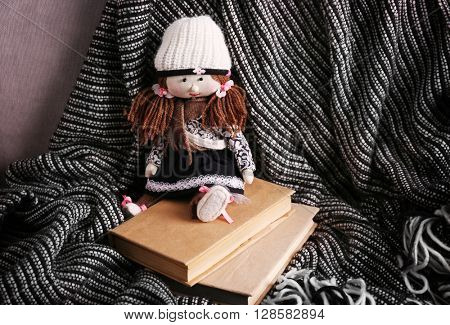 Rag doll with fairy tales books on bedspread. Childhood concept
