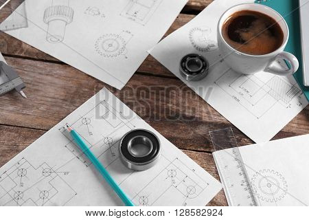 Set of engineering drawings with cup of coffee and tools on wooden background