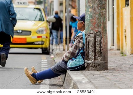 Banos De Agua Santa - 29 November : Old Hispanic Woman Sitting On The Roadside In A Bus Station South America In Banos De Agua Santa On November 29 2014