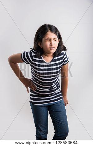 indian small girl having stomach ache, asian girl having pain in abdomen