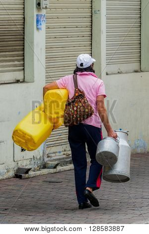 Banos, Ecuador - 29 November 2014: Hispanic Sales Woman Carrying Her Products On City Streets Of Banos De Agua Santa, South America In Banos On November 29, 2014