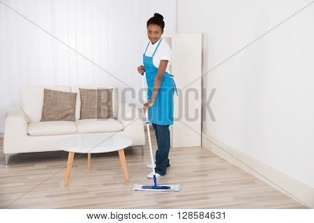 Young Happy Female Janitor Mopping Floor In Room